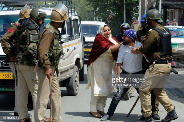 Indian security personnel detain a Kashmiri man during protests by students in Srinagar on April 11 following clashes that left three civilians dead...