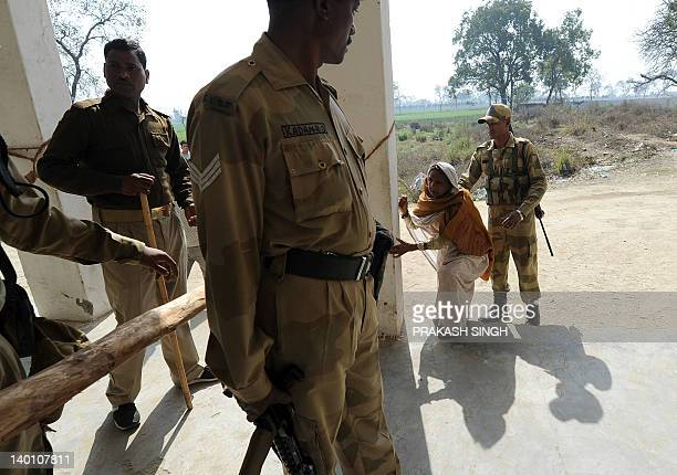 Indian security personnel helps an elderly woman reach a polling station in Meerut in Uttar Pradesh on February 28, 2012. The sixth phase of assembly...