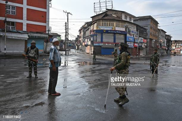 Indian security personnel question a man on a street during a curfew in Srinagar on August 8 as widespread restrictions on movement and a...
