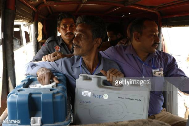 Indian security personnel sit in a vehicle next to the polling officers carrying electronic Voter Verifiable Paper Audit Trail machines and...