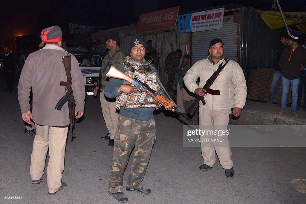 Indian security personnel stand alert on a road leading to the Air Force Base in Pathankot on January 2 2016 during an ongoing attack on the base by..