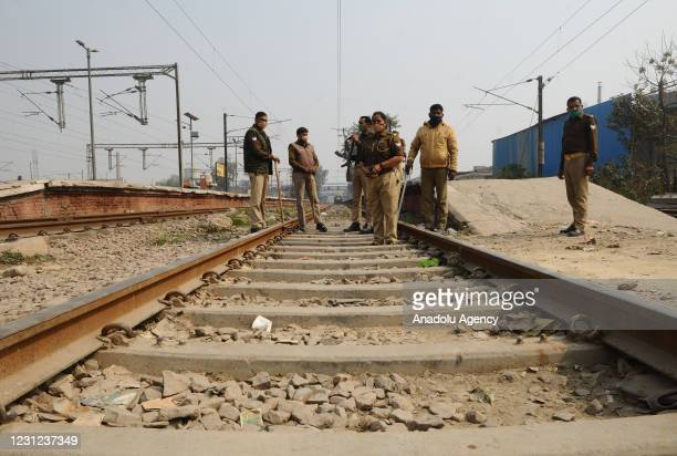Indian Security personnel stand guard as farmers block a railway track to stop train services at Modi Nagar railway station part of protests against...