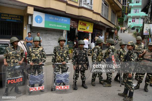 Indian security personnel stand guard on a streets in front of a shuttered ATM machine during an indefinite strike of government offices and banks...