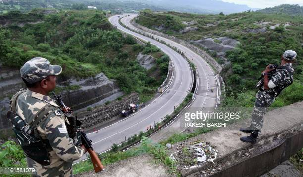 TOPSHOT Indian security personnel stand guard overlooking the JammuSrinagar highway in Nagrota near Jammu on August 14 2019