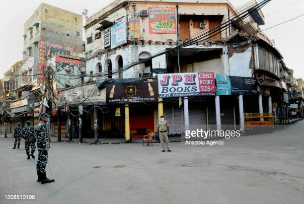 Indian security personnel stands guard in front of a closed shops during the nationwide lockdown, in wake of coronavirus pandemic, in old Delhi,...