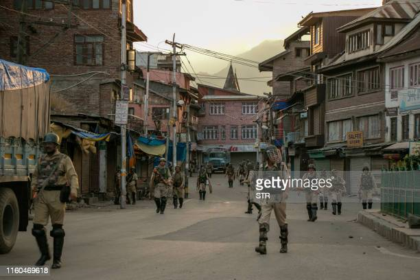 Indian security personnel walk on a street in Srinagar on August 9 as widespread restrictions on movement and a telecommunications blackout remained...
