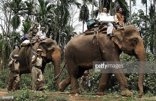 Indian security personnels escort election officials transporting Electronic Voting Machines on elephants leaving to polling stations of the Guwahati...