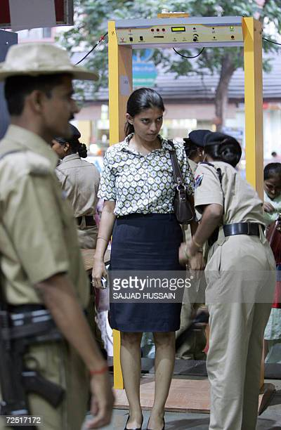 Indian security personnels frisk passengers as they walk through metal detector frames at the Churchgate railway station in Mumbai 13 Novembr 2006 In...