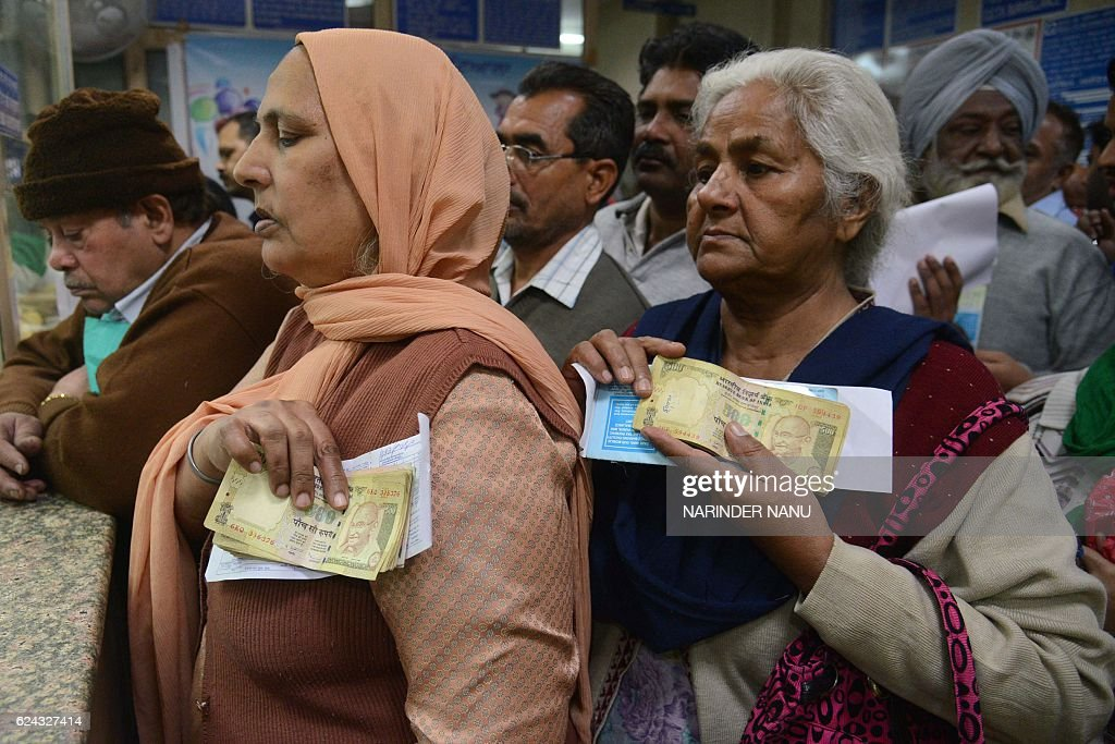 Indian senior citizens gather inside a bank as they wait to deposit and exchange 500 and 1000 rupee notes in Amritsar on November 19 2016 India`s...