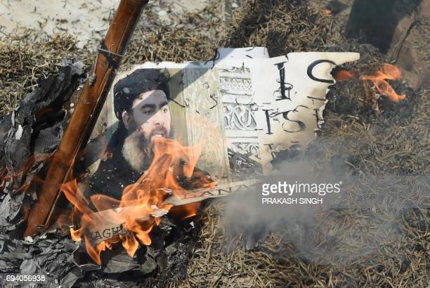 Indian Shiite Muslim demonstrators burn an effigy of the Islamic State group leader Abu Bakr al-Baghdadi during a protest in New Delhi on June 9,...