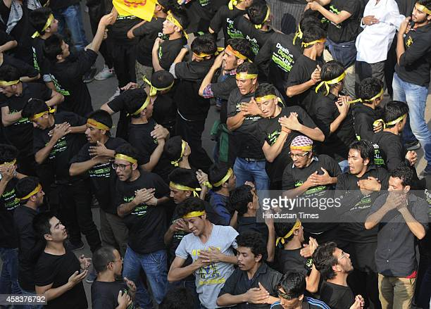 Indian Shiite Muslim men beat their chest as they mourn during a procession to mark Ashura on November 4 2014 in New Delhi India It is commemorated...
