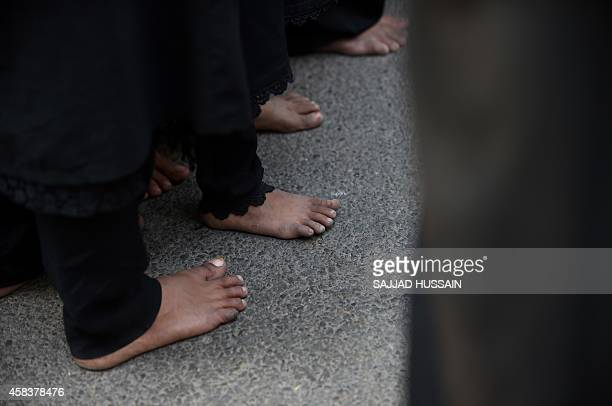 Indian Shiite Muslim women walk barefoot during an Ashura procession at Trilokpuri in eastern New Delhi on November 4 2014 Ashura mourns the death of...