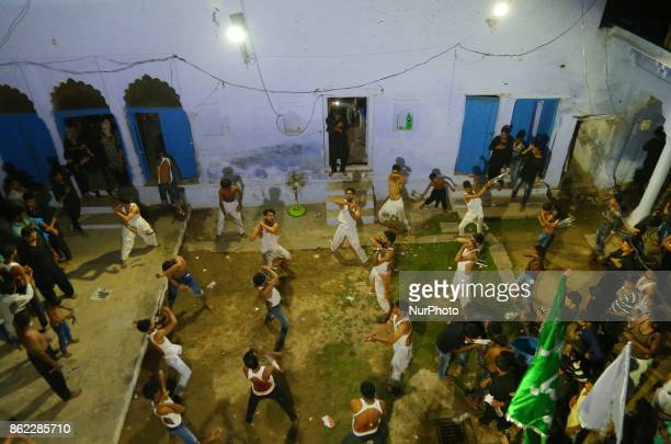 Indian shiite muslims beat their chests and flagellate to mark midnight Ashura procession in the old streets of Allahabad on October 172017 The...