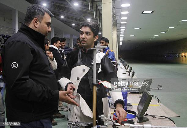 Indian shooter and Olympic gold medal winner Abhinav Bindra chats with compatriot Gagan Narang after winning 10metre Air Rifle event's final round at...
