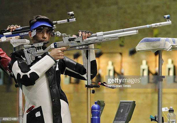 Indian shooter and Olympic gold medal winner Abhinav Bindra takes aim with rifle during 10metre Air Rifle event's final round at National Shooting...
