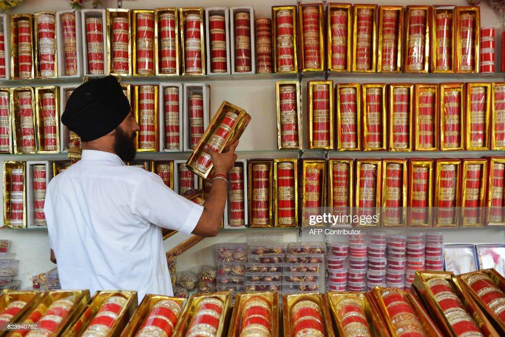 Indian shopkeeper Ajinder Singh displays wedding Chura at his shop in Amritsar on July 28 2017 / AFP PHOTO / NARINDER NANU