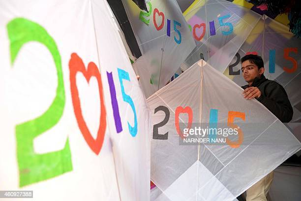 Indian shopkeeper Amit Kumar hangs kites at his shop in Amritsar on December 31 on New Years Eve AFP PHOTO/NARINDER NANU