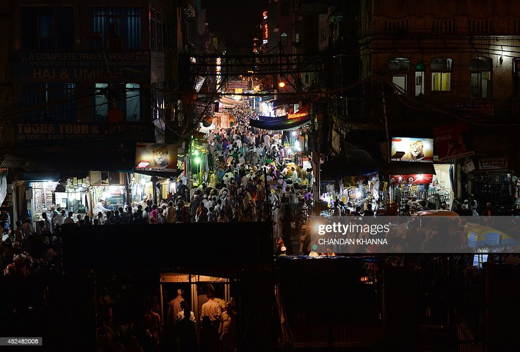 Indian shoppers walk through a market outside a mosque after the breaking of the Ramadan fast in New Delhi on July 21, 2014. During the holy month of Ramadan Muslims around the world focus on prayer, fasting, giving to charity, and religious devotion. AFP PHOTO/Chandan Khanna
