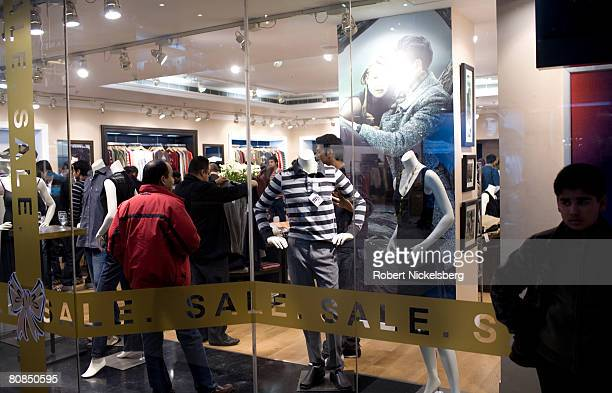 Indian shoppers walk through a Tommy Hilfiger clothing store in the Saket shopping mall in New Delhi India February 2 2008 India's middle class...