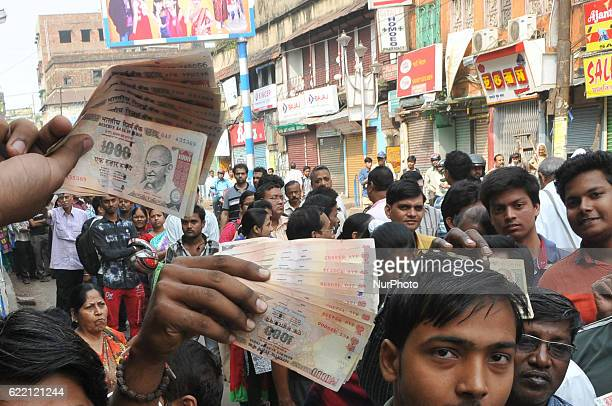 Indian Showing 1000 and 500 rupee and long time waiting a long line Many Deposit and change old to new currency at Front of STATE BANK OF INDIA...
