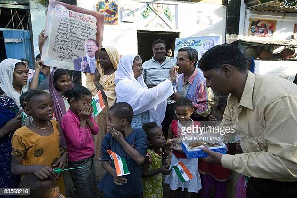 Indian Siddi Tribals hold posters of US Presidentelect Barack Obama and Indian National Flags and eat sweets as they gather in front of Hazarat...