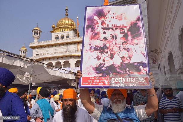 Indian Sikh activists from radical Sikh organisations hold a poster of Sri Akal Takhat Sahib as they shout slogans in support of Sikh leader Sant...
