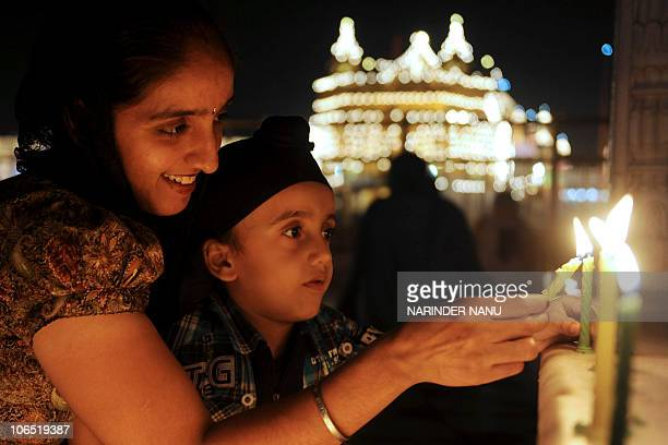 Indian Sikh devotee Amanpreet Kaur poses with her son Hargun Singh as they light candles in front of the illuminated Golden Temple in Amritsar on...