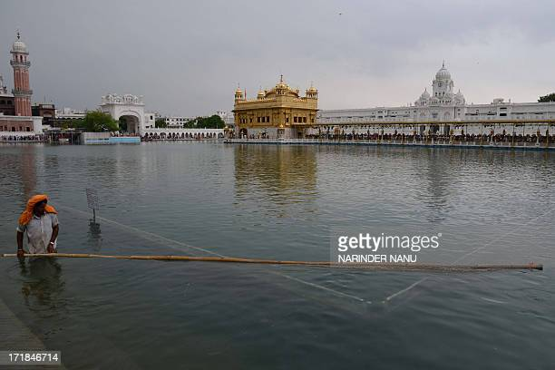 Indian Sikh devotee cleans the holy sarovar at the Sikh Shrine The Golden Temple in Amritsar on June 292013 On the occasion of the 174th death...