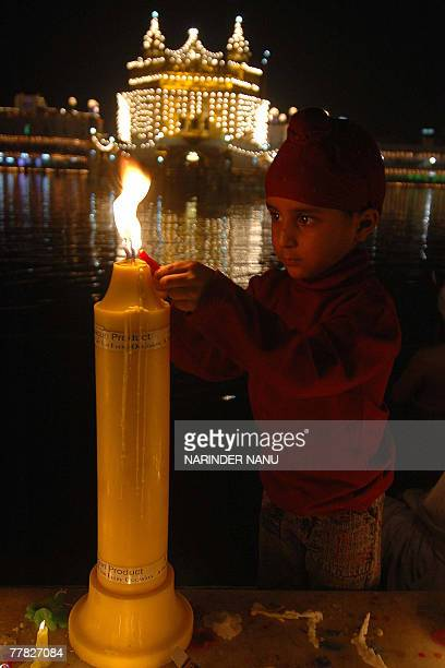 Indian Sikh devotee lights candles in the front of the illuminated Golden Temple on the occasion of Bandi Chhor Divas in Amritsar 09 November 2007...