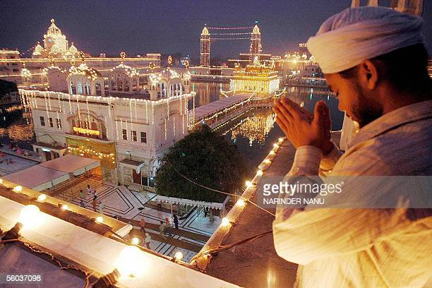 Indian Sikh devotee Sonu prays in front of the illuminated Golden Temple in Amritsar in India's northwestern state of Punjab 31 October 2005 on the...