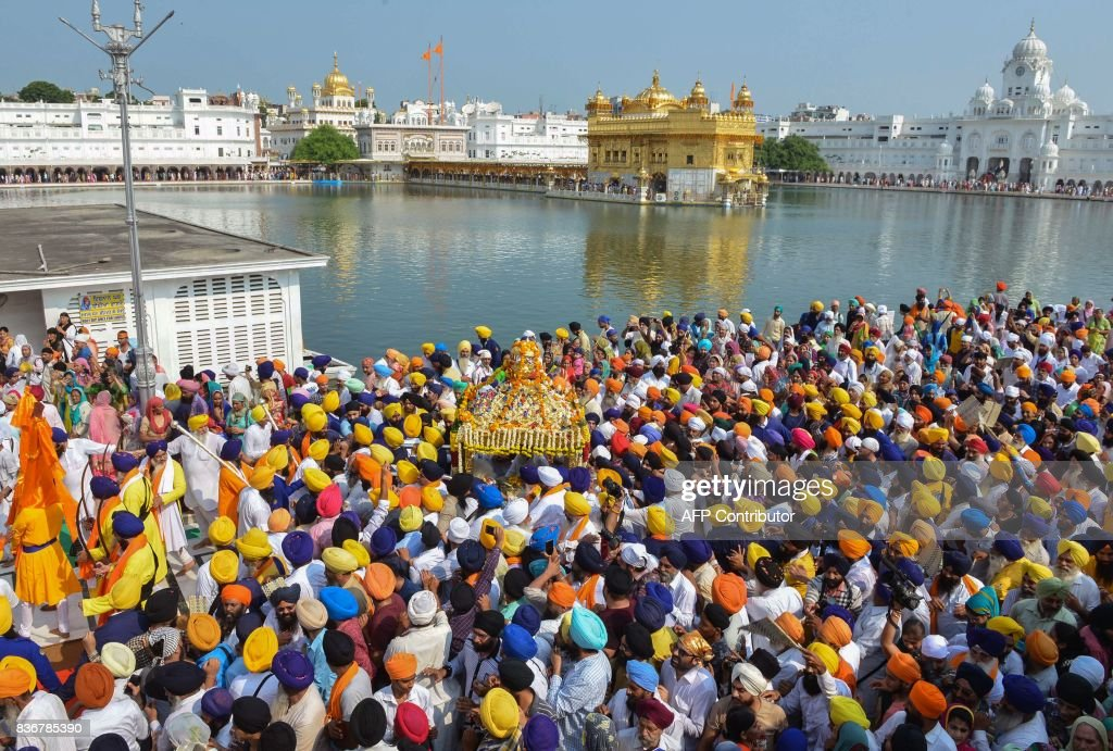 Indian Sikh devotees carry the Guru Granth Sahib the central religious text of Sikhism during a religious procession to mark the 413rd anniversary of.