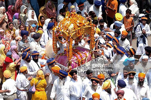 Indian Sikh devotees carry the Palki Sahib during a procession from the Lohgarh Sahib Gurdwara to the Santokh Sar Gurudwara in Amritsar on May 1on...