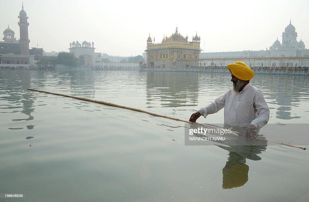 Indian Sikh devotees clean the water tank at the Sikh Shrine, the Golden Temple on the eve of the anniversary of the ninth guru of Sikhism, Sri Guru Teg Bahadur in Amritsar on November 23, 2012. Sri Guru Tegh Bahadur Sahib was born at Amritsar in 1621 and was the youngest son of Sri Guru Hargobind Sahib.
