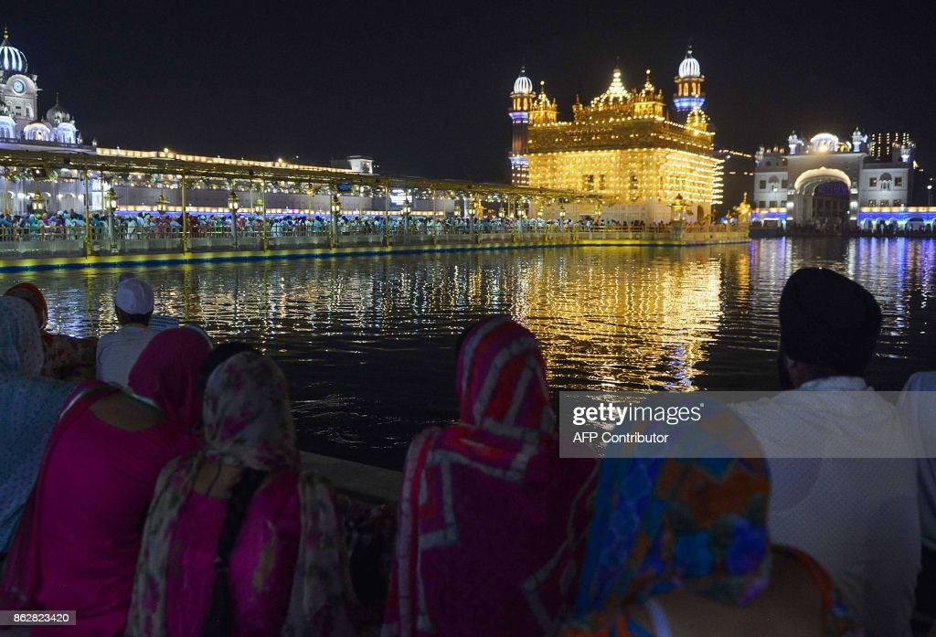 Indian Sikh devotees gather during Diwali Festival at the illuminated Golden Temple in Amritsar on October 18 2017 Diwali the Hindu festival of...