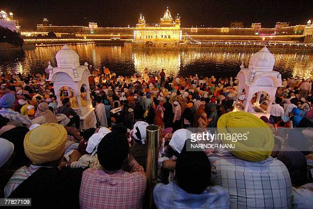 Indian Sikh devotees gather in the front of the illuminated Golden Temple on the occasion of Bandi Chhor Divas in Amritsar 09 November 2007...