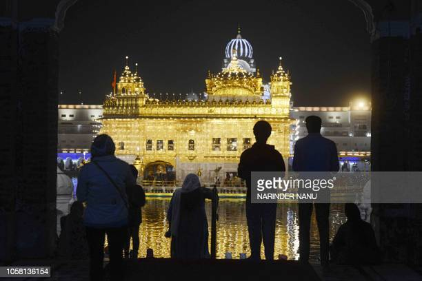TOPSHOT Indian Sikh devotees gather to pay their respects as lights glow on the eve of Bandi Chhor Divas or Diwali festival at the Golden Temple in...