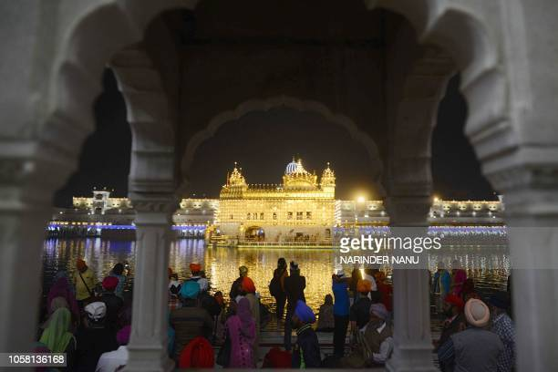 Indian Sikh devotees gather to pay their respects as lights glow on the eve of Bandi Chhor Divas or Diwali festival at the Golden Temple in Amritsar...