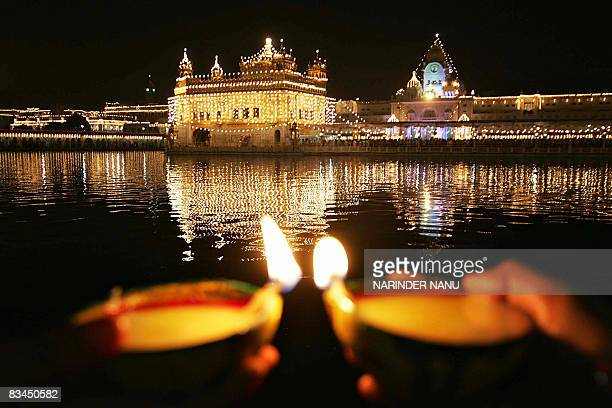 Indian Sikh devotees hold 'diyas' as they offer prayers in front of the illuminated Golden Temple on the eve of the festival of Bandi Chhor Divas in...