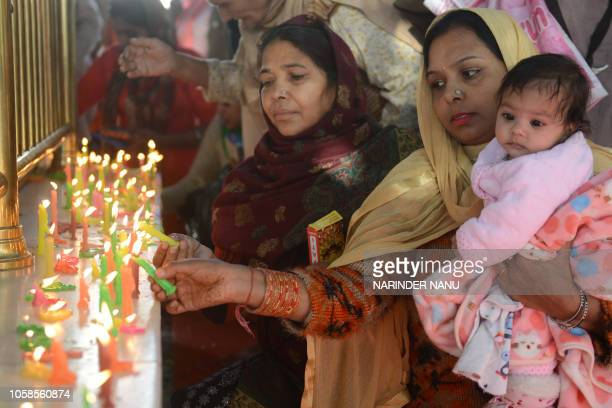 Indian Sikh devotees light candles as they gather to pay their respects on the occasion of Bandi Chhor Divas at the Golden Temple in Amritsar on...