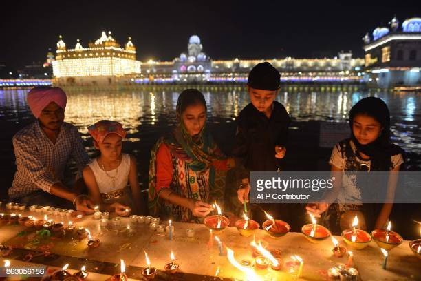 Indian Sikh devotees light candles as they mark Bandi Chhor Divas or Diwali at the Golden Temple in Amritsar on October 19 2017 Sikhs celebrate Bandi...