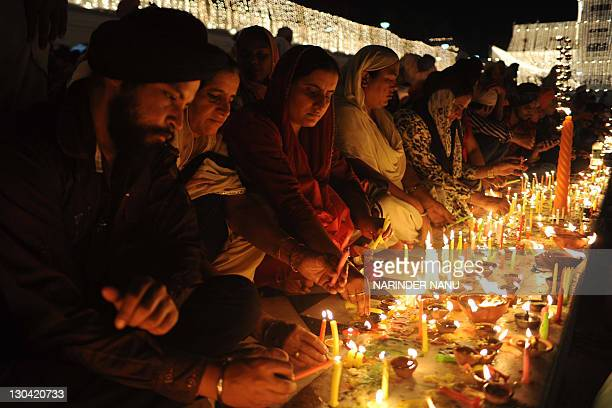 Indian Sikh devotees light candles as they pay their respects at the illuminated Sikh Shrine The Golden Temple in Amritsar on October 26 on the...