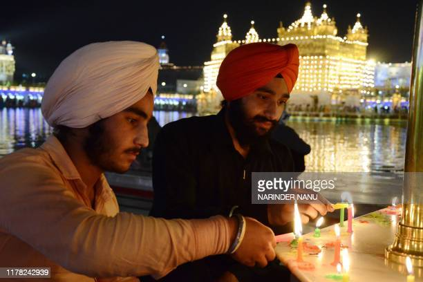 Indian Sikh devotees light candles as they pay their respects on the eve of Bandi Chhor Divas or Diwali at the illuminatedGolden Temple in Amritsar...
