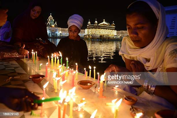 Indian Sikh devotees light candles at the illuminated Sikhism's holiest shrine Golden Temple in Amritsar on November 2 on the eve of Bandi Chhor...