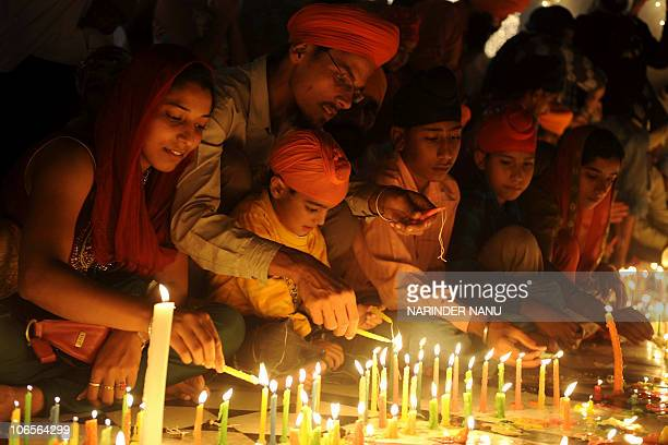 Indian Sikh devotees light candles at the Sikh Shrine Golden Temple at dusk in Amritsar on November 5 on the occasion of Bandi Chhor Divas or Diwali...