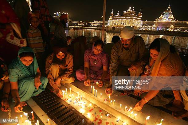 Indian Sikh devotees light candles in front of the illuminated Golden Temple in Amritsar on October 28 2008 on the occasion of the festival of Bandi...