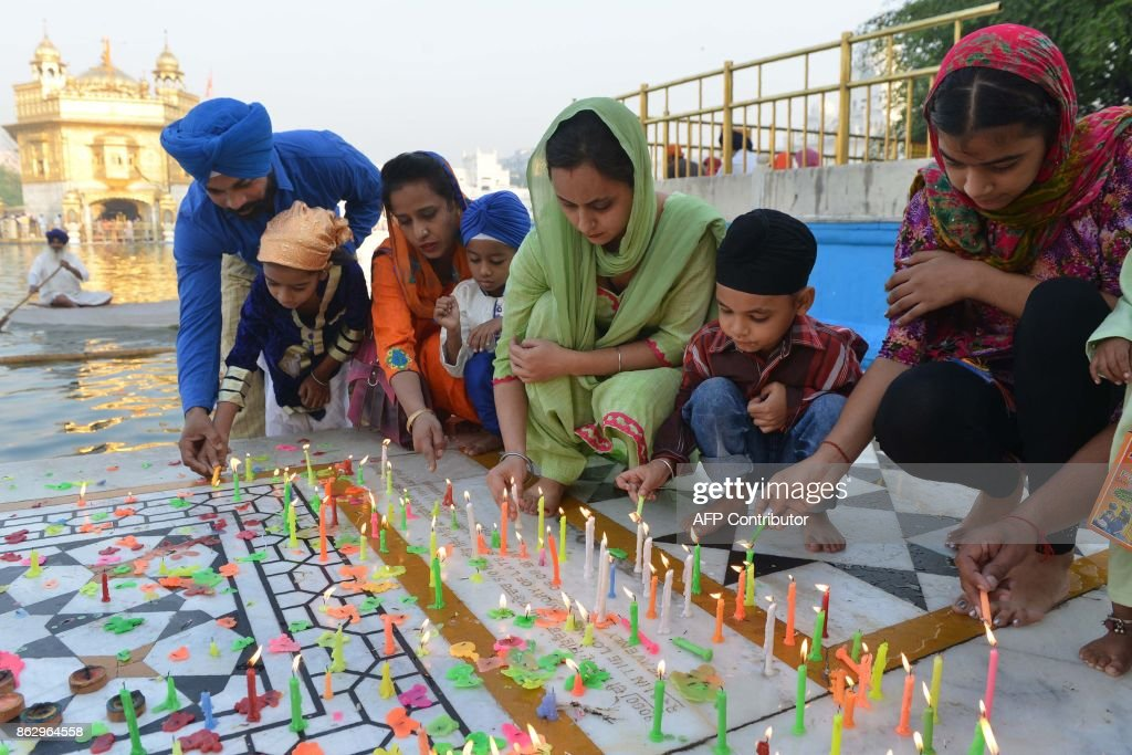 Indian Sikh devotees light candles in the early morning during Diwali Festival at the illuminated Golden Temple in Amritsar on October 19 2017 Diwali.