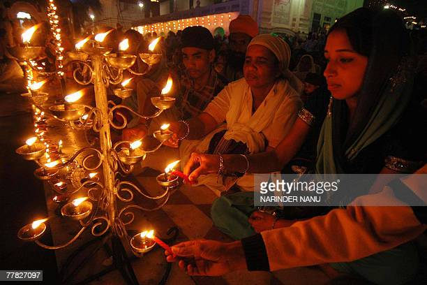 Indian Sikh devotees light candles in the front of the illuminated Golden Temple on the occasion of Bandi Chhor Divas in Amritsar 09 November 2007...