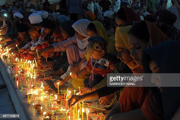 Indian Sikh devotees light candles on the occasion of Bandi Chhor Divas or Diwali at the illuminated Golden Temple in Amritsar India on October 23...