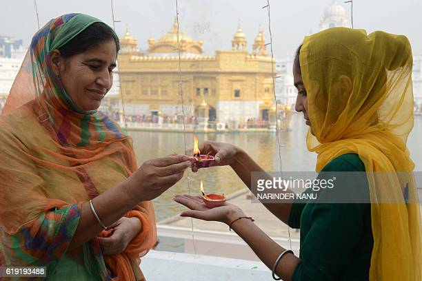 Indian Sikh devotees light 'diyas' as they pay respects on the occasion of Bandi Chhor Divas or Diwali at the Golden Temple in Amritsar on October 30...