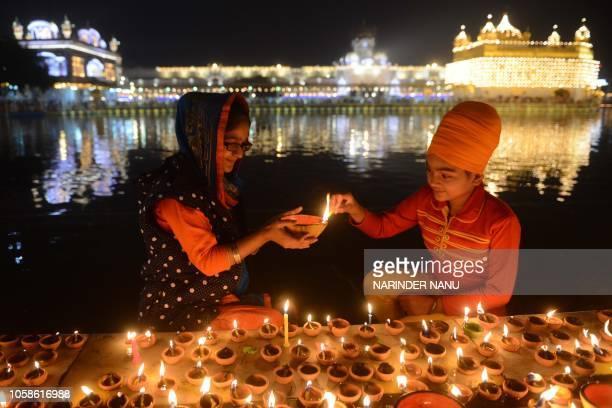 Indian Sikh devotees light lights diyas during Bandi Chhor Divas or Diwali at the Golden Temple in Amritsar on November 7 2018 Sikhs celebrate 'Bandi...